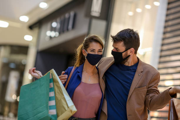 The young couple carries shopping bags and walks through the mall, both wearing protective masks and looking at each other, life during pandemic stock photo
