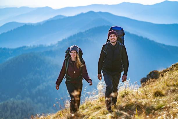 la joven pareja va a la montaña - excursionismo fotografías e imágenes de stock