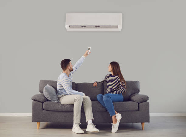 The young couple turns on the air conditioner cools the air while sitting on the sofa in the room stock photo