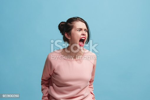 istock The young emotional angry woman screaming on blue studio background 922830250