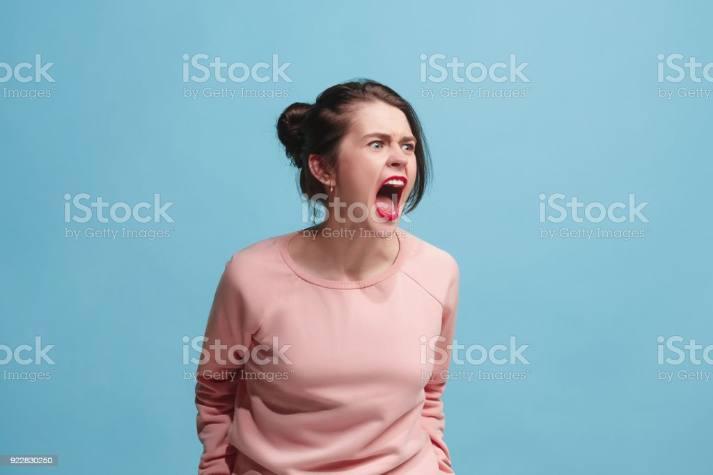 The young emotional angry woman screaming on blue studio background stock photo