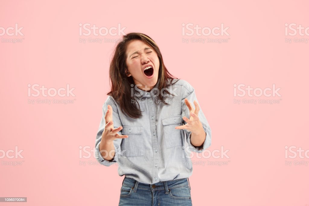 The young emotional angry woman screaming on studio background stock photo