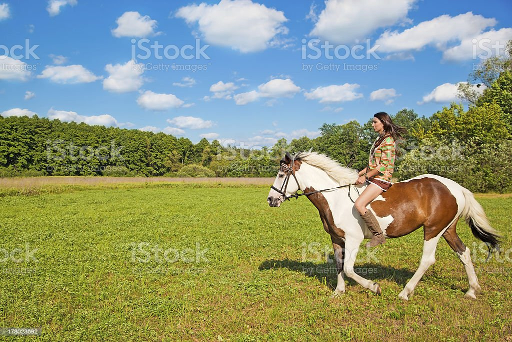 The young girl rides a paint horse royalty-free stock photo
