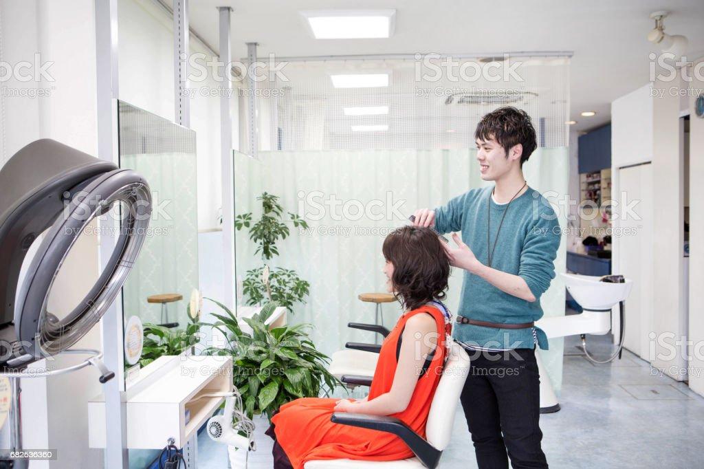 若い美容師が女性の髪を終了 ストックフォト