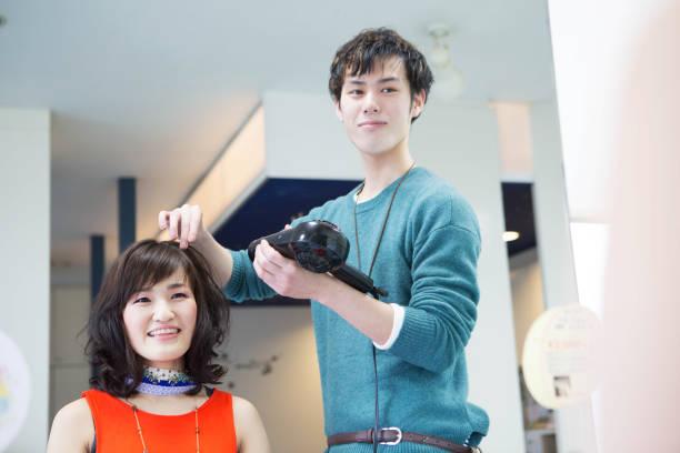 若い美容師が女性の髪を終了 - 美容院 ストックフォトと画像
