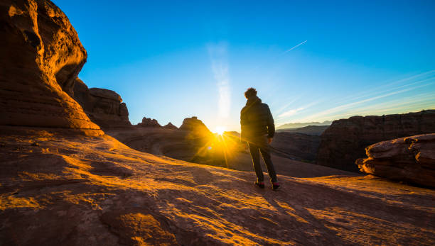 The young hipster man, traveler and hiker, admiring the sunrise in the red canyon near by Delicate Arch, Utah, at sunrise stock photo