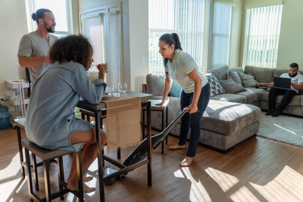 Die junge Hispanic/Latino Frau, die die gemeinsame Wohnung mit einem Staubsauger putzt, wenn ihre Freunde-Mitbewohner haben etwas Essen in der Küche, und eine andere Mitbewohnerin, die auf einer Couch in einem Wohnzimmer mit PC-Laptop. – Foto