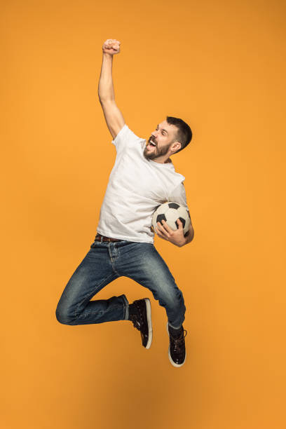 the young man as soccer football player kicking the ball at studio - soccer supporter portrait imagens e fotografias de stock