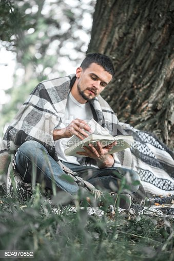 862602714 istock photo The young man at the tree reading a book 824970852