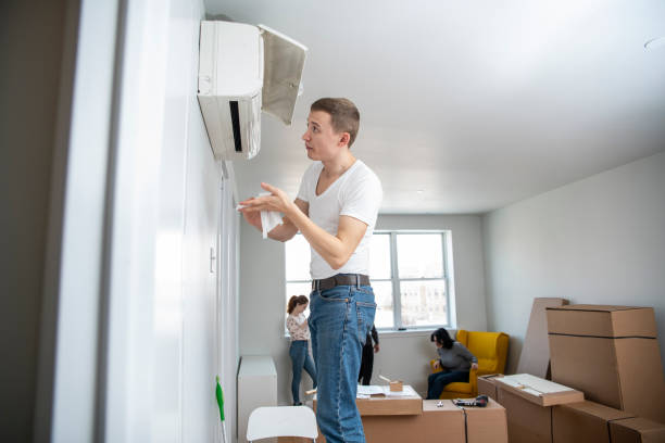 The young man cleaning filters in the air-conditioning split device in the recently rented apartment stock photo
