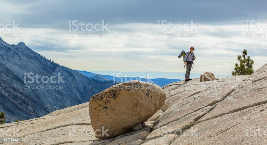 The young man, hipster, tourist - hiker and backpacker, observing the Yosemite from the  Olmsted Point stock photo
