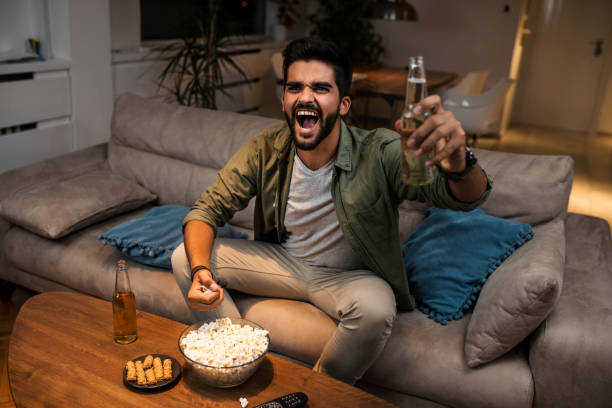 The young man is watching a sports game on TV The young man is watching a sports game on TV man cave couch stock pictures, royalty-free photos & images