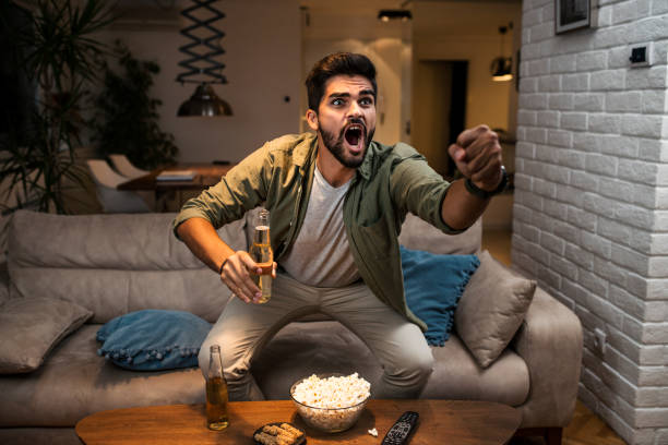 The young man is watching a sports game on TV stock photo
