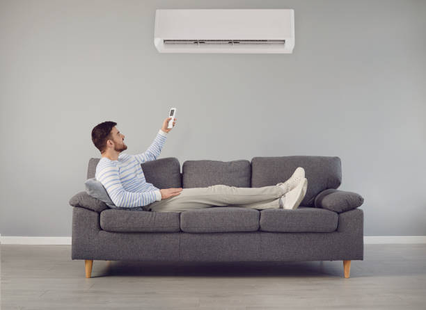 The young man turns on the air conditioner cools the air while sitting on the sofa in the room stock photo
