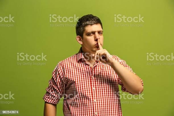 Foto de O Jovem Sussurrar Um Segredo Por Trás De Sua Mão Sobre Fundo Verde e mais fotos de stock de Adulto