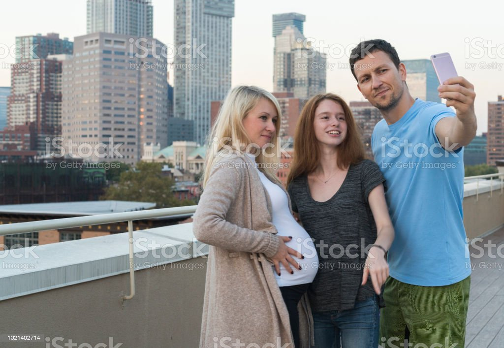 The young married Caucasian white family, the man and the pregnant woman with her little sister, the 16 years old teenager girl, hanging out together, taking selfies pictures with the smartphone and having fun at the rooftop - foto stock