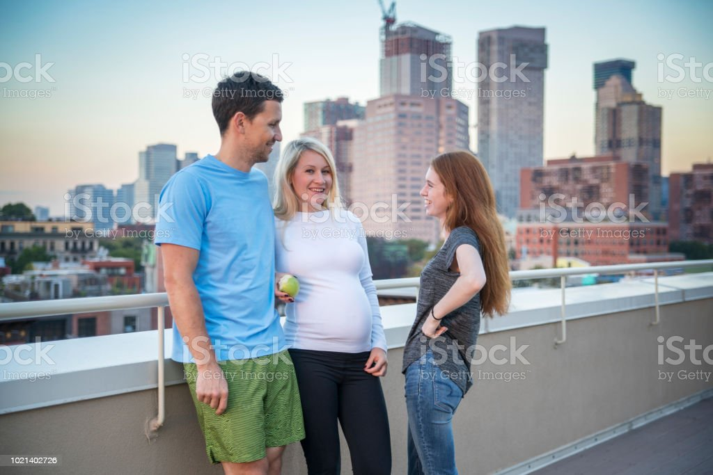 The young married Caucasian white family, the man and the pregnant woman with her little sister, the 16 years old teenager girl, hanging out together and having fun at the rooftop - foto stock