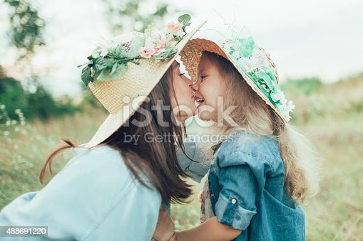 istock The young mother and daughter on green grass background 488691220