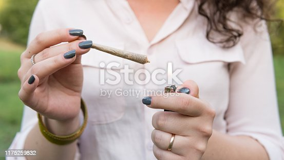The young person smoking medical marijuana joint outdoors. The young woman smoke cannabis blunt, close-up. Cannabis is a concept of herbal alternative medicine.