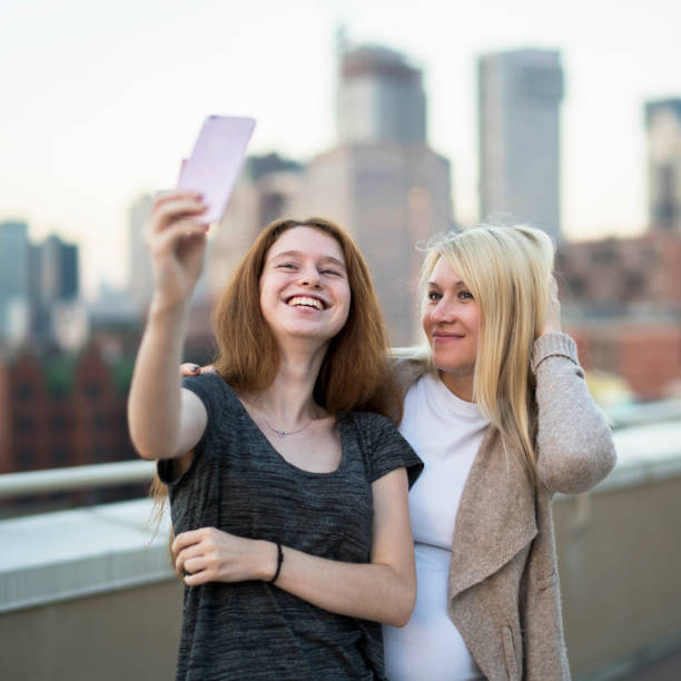 The young pretty pregnant woman with her little sister, the 16 years old teenager girl, hanging out together, taking selfies pictures with the smartphone and having fun at the rooftop - foto stock