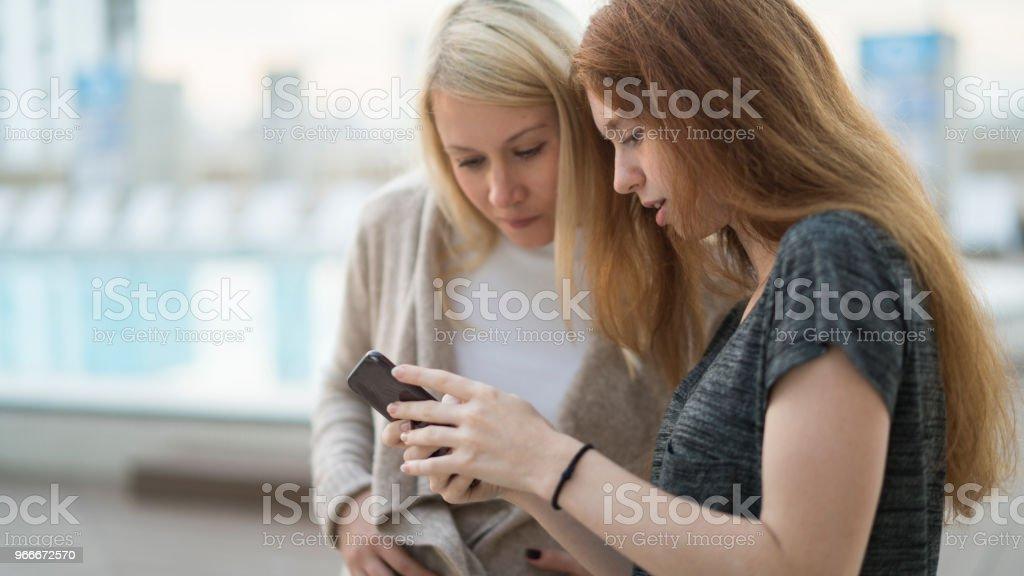 La jeune femme enceinte jolie avec sa petite soeur, la fille d'adolescent âgé de 16 ans, sortir ensemble, à la recherche d'images et la navigation sicial médias avec le smartphone et s'amuser sur le toit - Photo