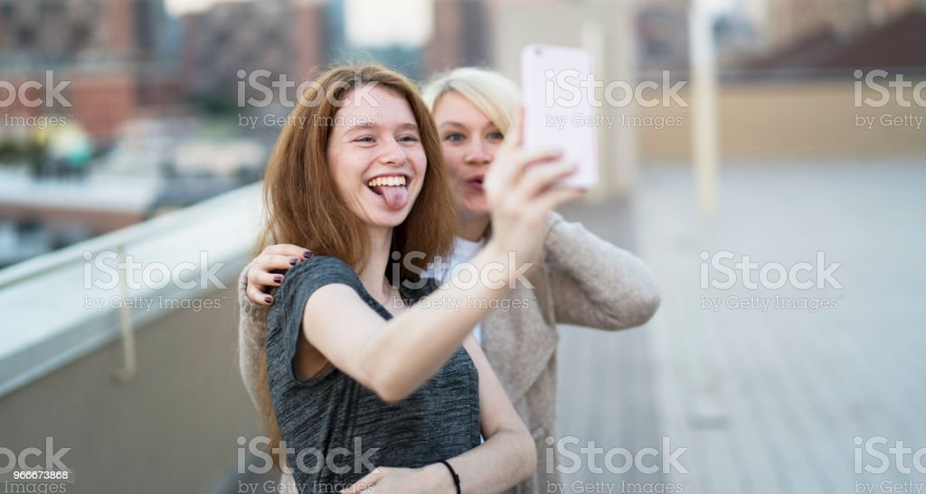 La jeune femme enceinte jolie avec sa petite soeur, la fille d'adolescent âgé de 16 ans, sortir ensemble, de prendre des photos de selfies avec le smartphone et de s'amuser sur le toit - Photo