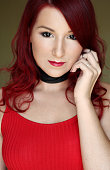 The young redhead woman in red top with black ribbon on the neck portrait