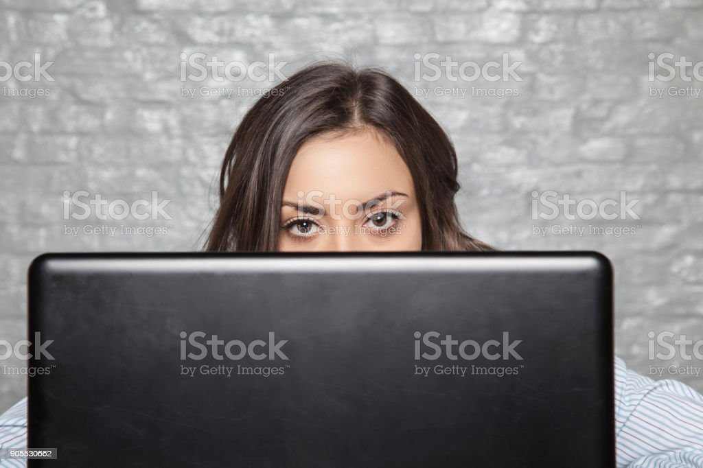 the young secretary hides behind the monitor stock photo