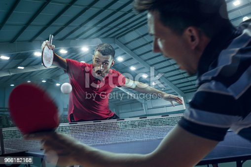The two young sports men tennis players in play on black sport arena background with lights. 3D model of the stadium was created by me (the author). Collage