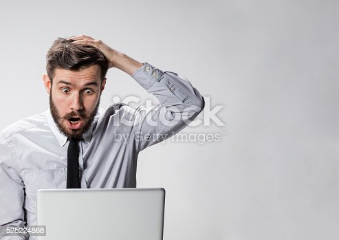 istock The young surprised man with his laptop computer 525224868