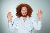 The young surrendered man with long red hair looking at camera with hands raised