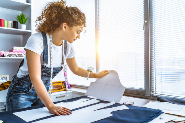 The young tailor sews a dress on the table The young tailor sews a dress on the table sun shining through dresses stock pictures, royalty-free photos & images