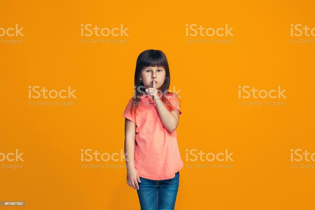 A jovem adolescente sussurrar um segredo por trás de sua mão sobre fundo  laranja foto royalty