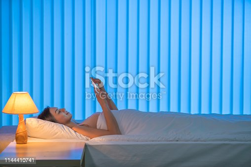 istock The young woman lay on the bed and phone. Evening night time 1144410741