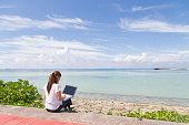 海でパソコンを操作する若い女性