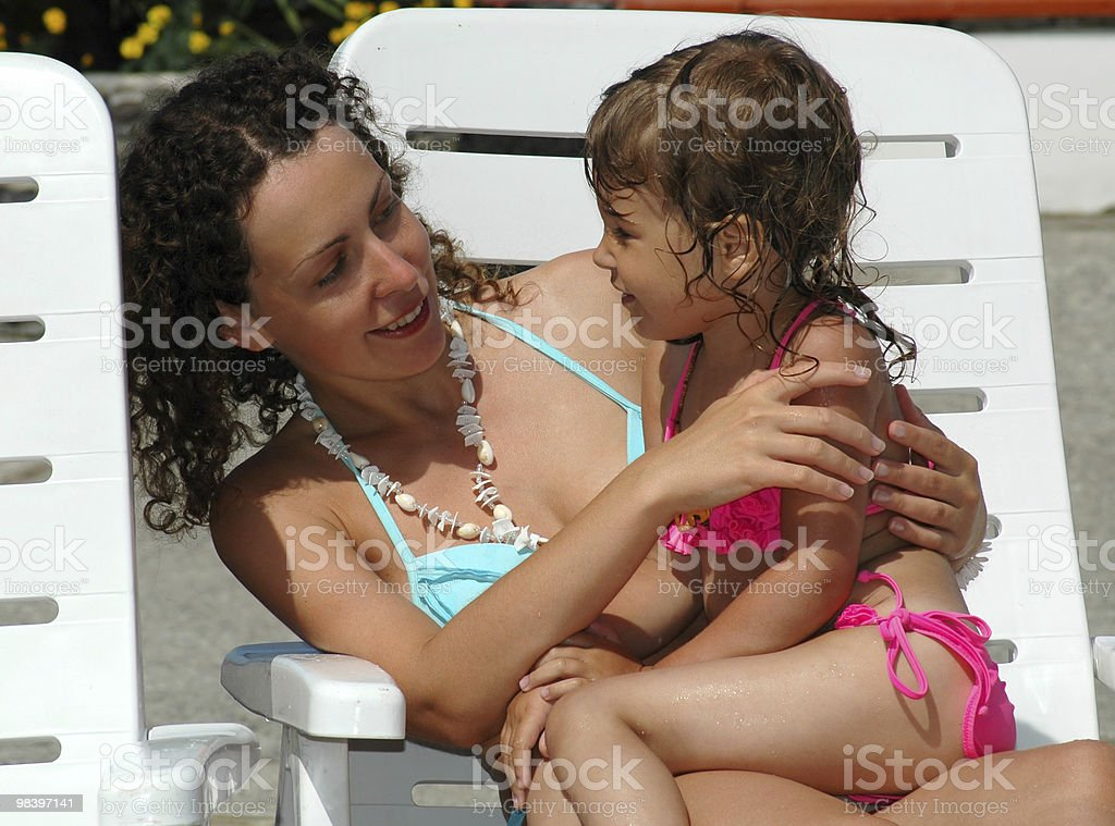 The young woman with child sit in a chaise lounge royalty-free stock photo