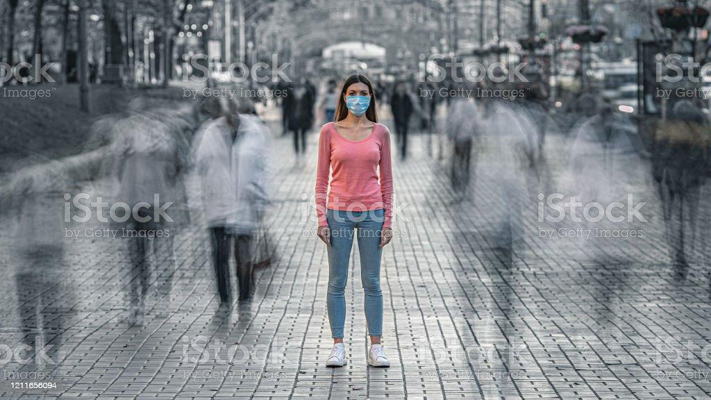 La joven con máscara médica en la cara se encuentra en la calle llena de gente - Foto de stock de Adulto libre de derechos