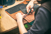 The young woman works with leather