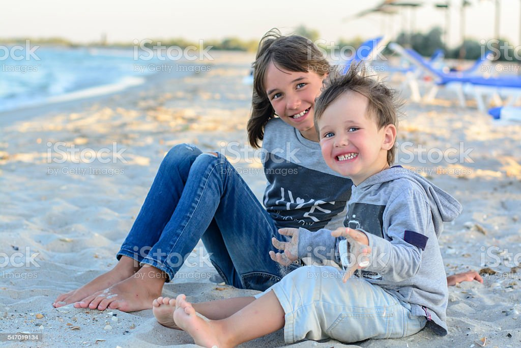 The younger brother and sister sitting on the beach stock photo