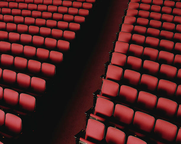 Theater aisle between red seats, overhead view stock photo