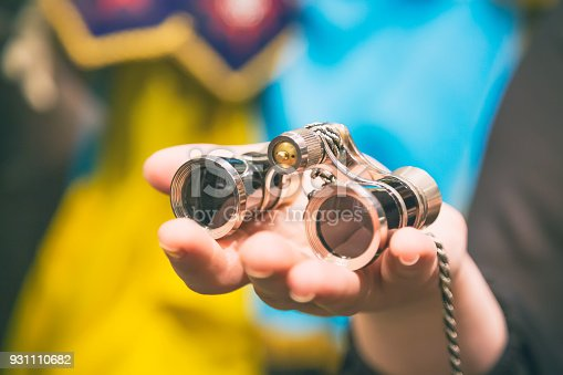 istock Theater concept. Vintage binoculars in female hand in theatre or opera 931110682