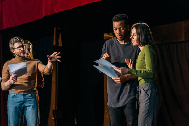 theater director, multicultural actors and actress rehearsing on stage stock photo