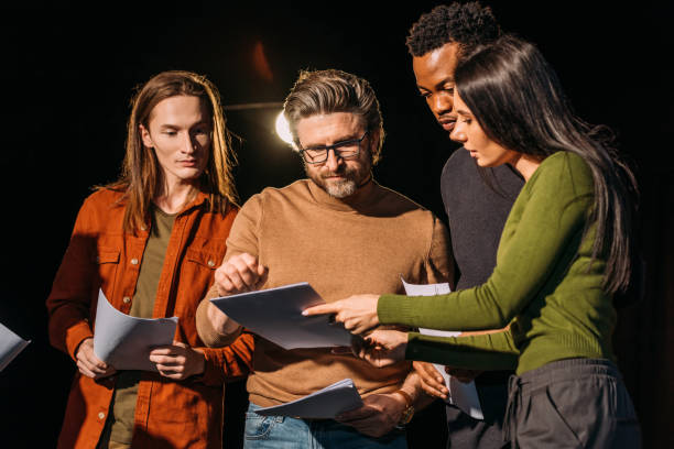 theater director, multicultural actors and actress rehearsing with scripts on stage stock photo