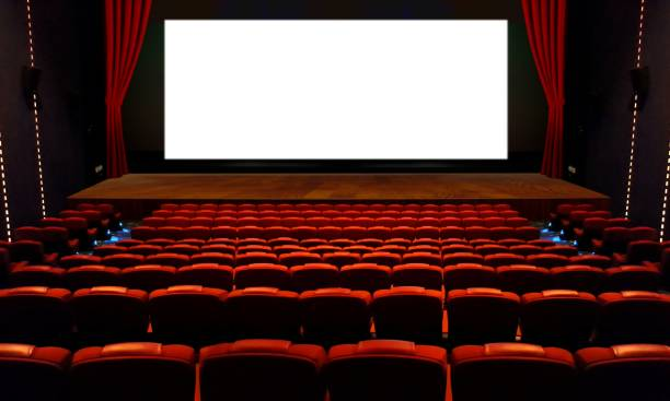 Theater hall with red seat and wide blank white screen stock photo