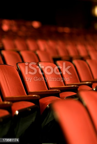 Rows and rows of Red theater seats.  Shallow depth of field. Vertical photograph.  Lots of room for copy.