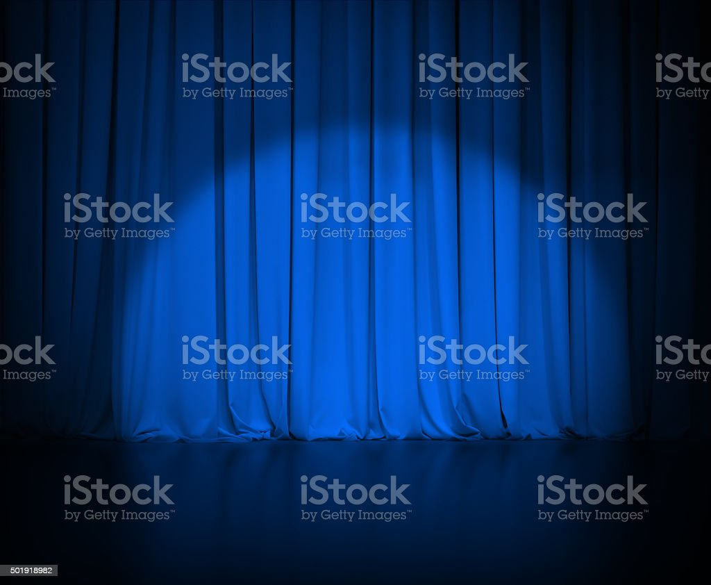 theatre dark blue curtain or drapes with light spot stock photo