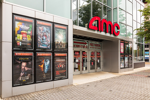 Chattanooga, TN, USA-10 May 2021: Diagonal front view of the downtown AMC theatre, shows sign-logo, entrance and current movie posters.