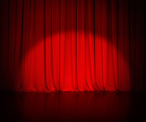 theatre red curtain or drapes background with light spot stock photo