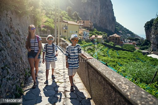 Brothers and sister hiking in Campania, Italy. Kids are walking the path from the town of Amalfi to the Valle delle Ferriere. Lemon trees and Amalfi visible in the background. Nikon D850