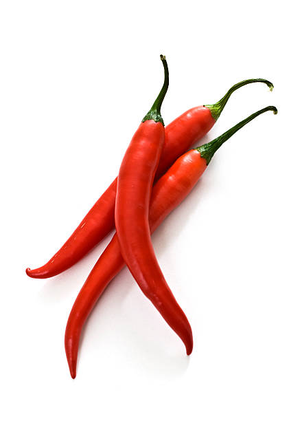 Thee red chili peppers against a white background stock photo